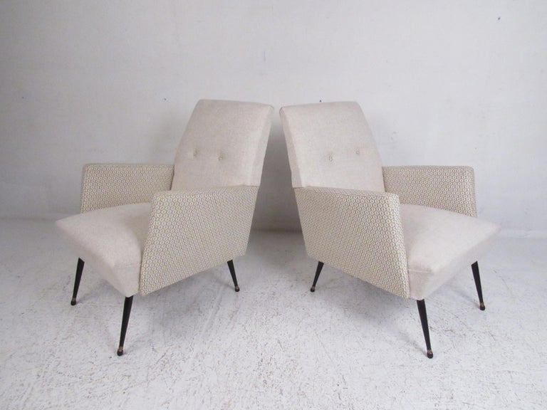 This beautiful pair of vintage modern armchairs feature cream-colored fabric with decorative armrests. The plush upholstery, tufted backrest, and splayed legs add to the midcentury appeal. This stylish pair of chairs make the perfect addition to any