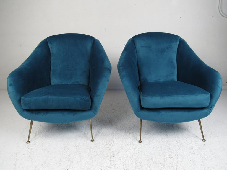 This elegant pair of vintage modern lounge chairs feature beautiful blue velour fabric and splayed brass legs. A sleek design in the style of Gio Ponti, that offers maximum comfort in any seating arrangement. The sloped armrests, drumstick shaped