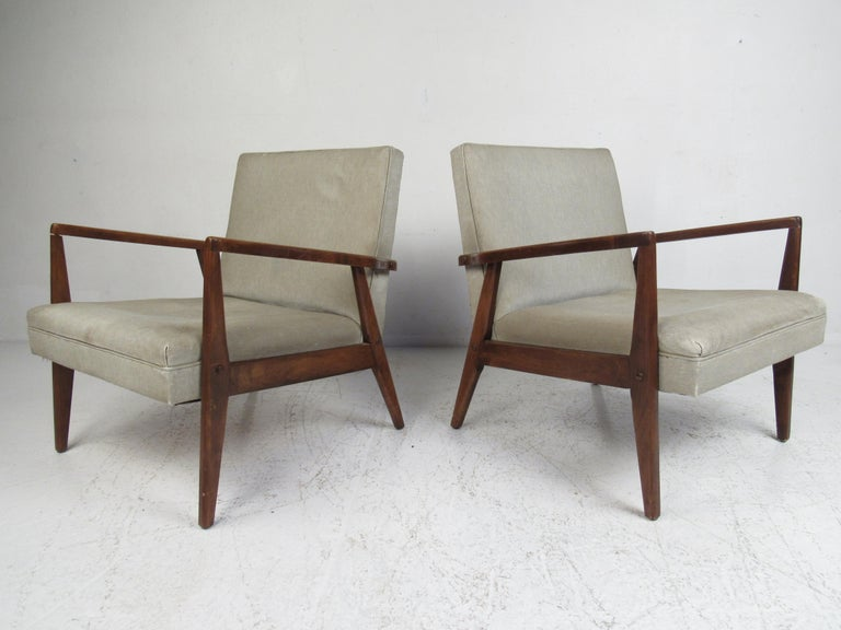 A stunning pair of vintage modern Italian lounge chairs with sculpted armrests and angled back legs. The sleek design ensures maximum comfort without sacrificing style. Please confirm item location (NY or NJ).