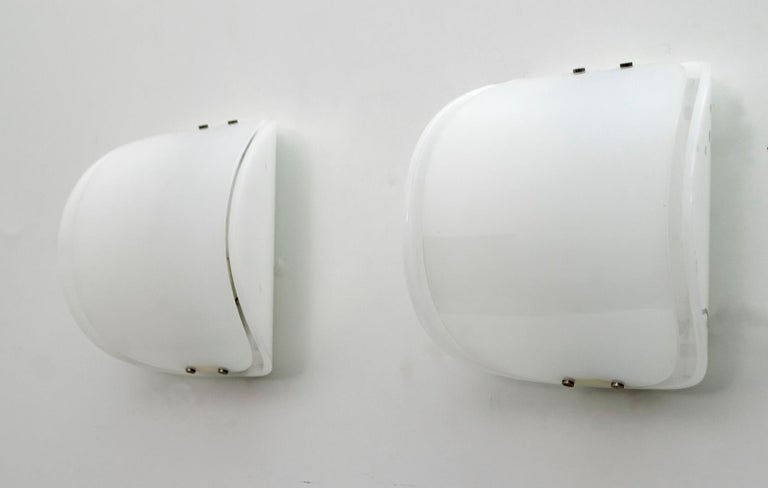 Set of two wall lamps with plexiglass body and metal details.