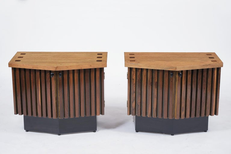 A sleek pair of midcentury nightstands that are made out of rosewood and mahogany that is newly stained in walnut and ebonize color combination and lacquered finish. They feature a flat top with a double door center, and the interior has plenty of