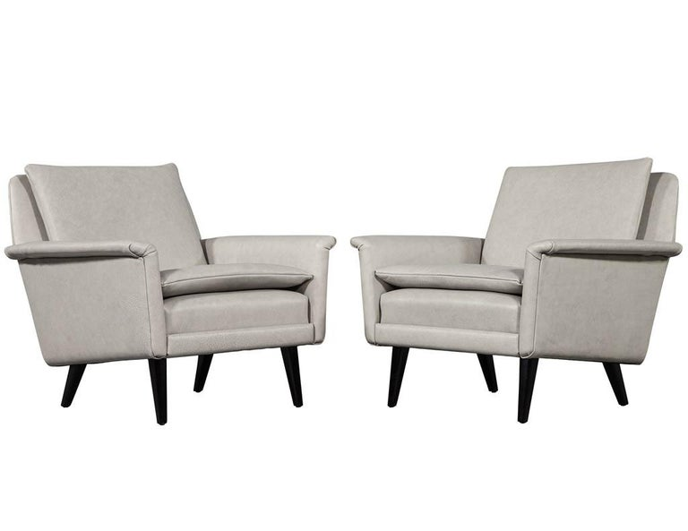 Pair of Mid-Century Modern leather lounge chairs. Restored Mid-Century Modern arm chairs reupholstered in a designer leather covering.  Price includes complimentary scheduled curb side delivery service to the continental USA.