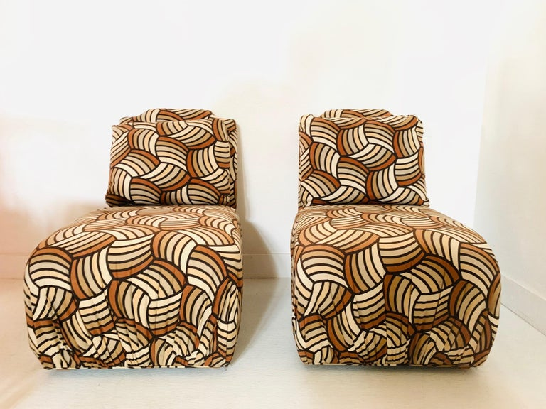 Pair of Mid-Century Modern lounge chairs. Original fabric, loose back cushions, and wood feet.