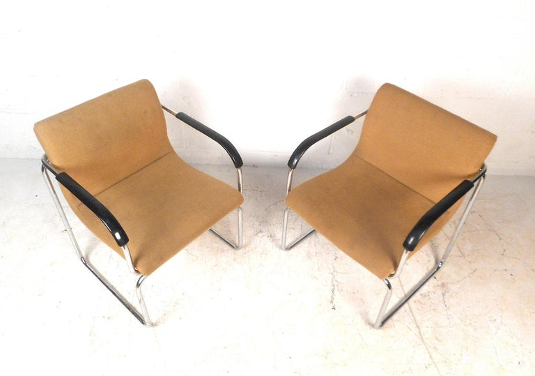 This impressive pair of vintage modern lounge chairs features a sturdy chrome frame and a form-fitting backrest. The chairs are upholstered with a comfortable sand-colored fabric. These Art Deco style lounge chairs will provide a seating arrangement