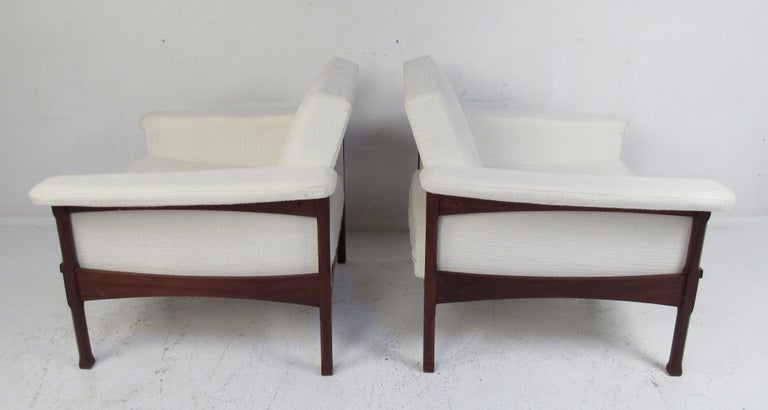 This beautiful pair of vintage modern lounge chairs feature sculpted dark wood frames with plush white fabric. The unique design boasts a floating backrest and upholstered armrests. The tapered legs have beveled edges showing quality craftsmanship.