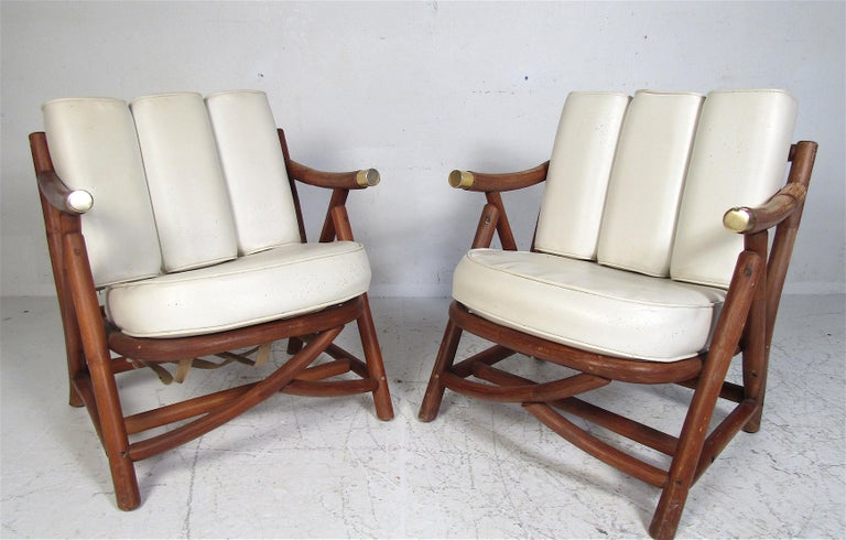 This unusual pair of vintage modern lounge chairs feature a cylindrical wood frame and two thick padded cushions. This sturdy and stylish pair ensures maximum comfort. The slatted backrest and brass capped armrests show true quality craftsmanship.