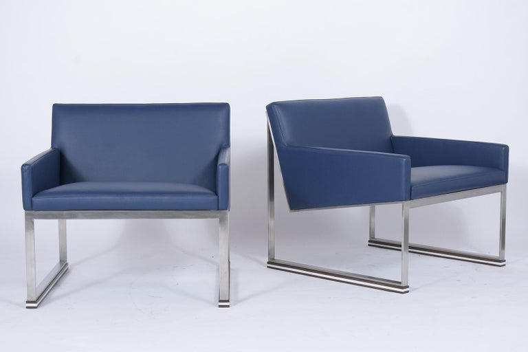 A pair of modern lounge chairs crafted out of steel, that have been newly restored and are in great condition, The chairs feature a comfortable wide seat and has been newly upholstered in blue leather with topstitch details held up by sturdy