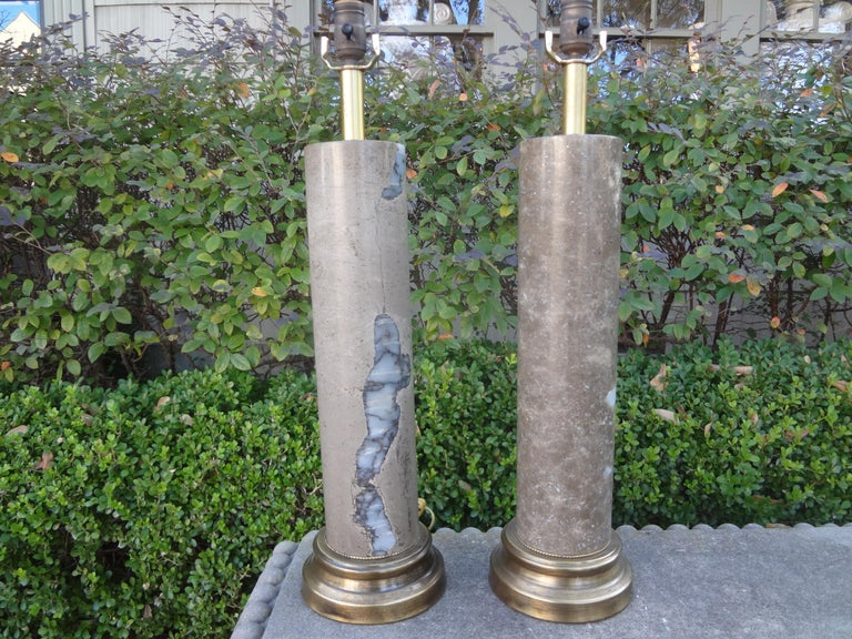 Gorgeous tall pair of cylindrical modernist marble table lamp, possibly Italian. The marble on each column lamp is unique yet this is a pair. This pair of Hollywood Regency lamps have been newly wired for the U.S. market and would work well in a