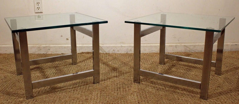Offered is a pair of end tables designed by Milo Baughman. They feature chrome bases with removable glass tops. They are in good condition for their age, showing some wear. They are not signed.