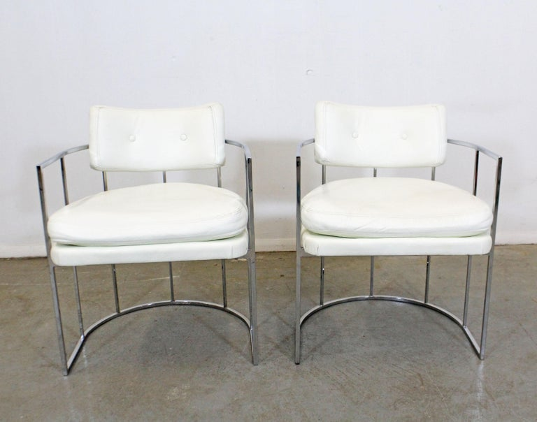 What a find. Offered is a pair of sleek and elegant vintage Mid-Century Modern chrome arm chairs. They were designed by Milo Baughman for Thayer Coggin. These chairs are having chrome bases with rounded backs and white vinyl upholstery. They're in