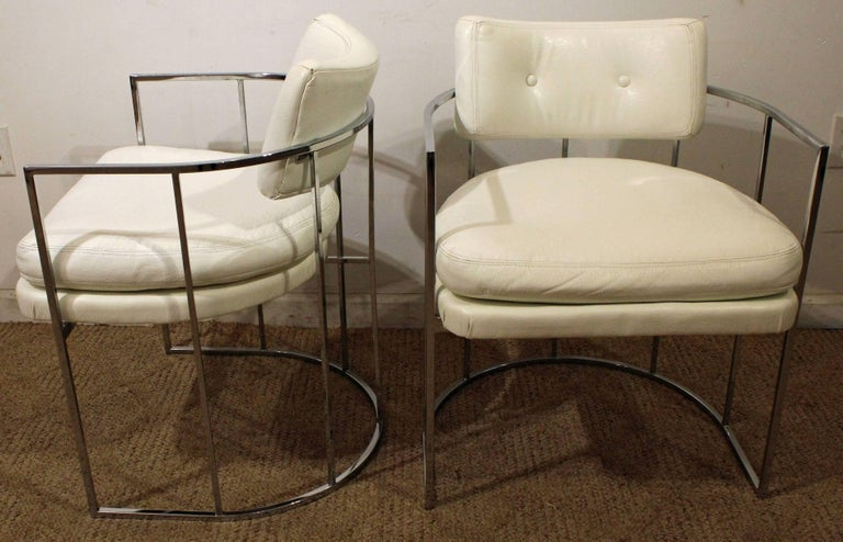 These chairs feature white vinyl upholstery and barrel-back chrome bases. They are signed by Thayer Coggin.  Measure: 22