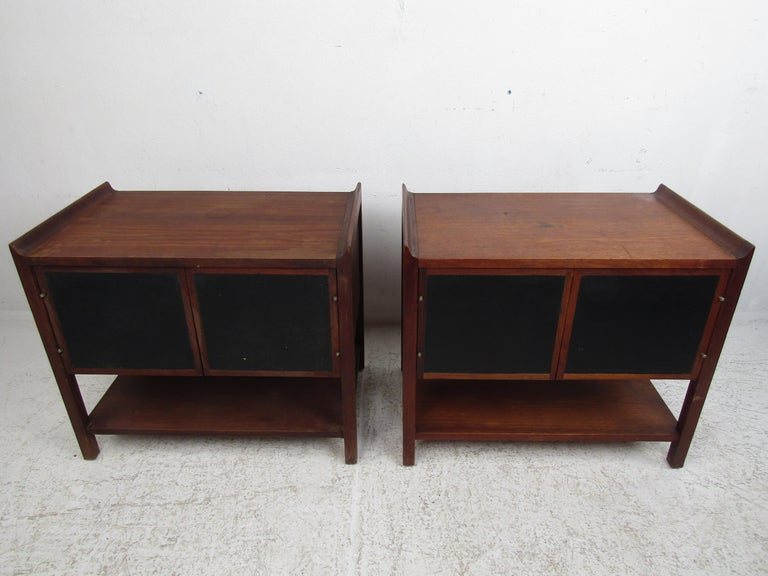 Stylish pair of Mid-Century Modern nightstands, striking design with raised edges on the tabletops, and leather-front accents on the cabinet doors. This pair is sure to make a great addition to any modern interior. Please confirm item location with