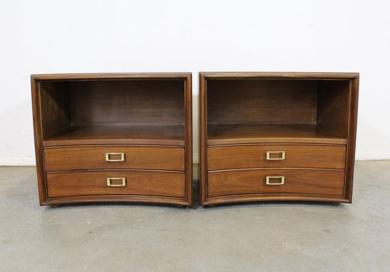 Offered is a pair of Mid-Century Modern nightstands designed by Paul Frankl for Johnson Furniture's 'Emissary' line. These stands feature curved fronts, two drawers each, and brass hardware. They have been refinished with a walnut stain. In very