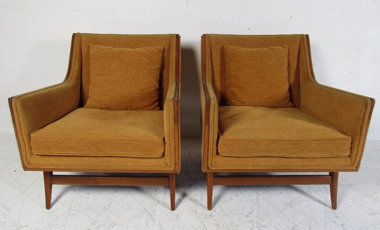 This beautiful pair of vintage modern armchairs feature plush orange colored upholstery and a sturdy walnut frame. The splayed legs and sloped armrests show quality craftsmanship. A thick padded seat cushion and backrest pillow ensure optimal