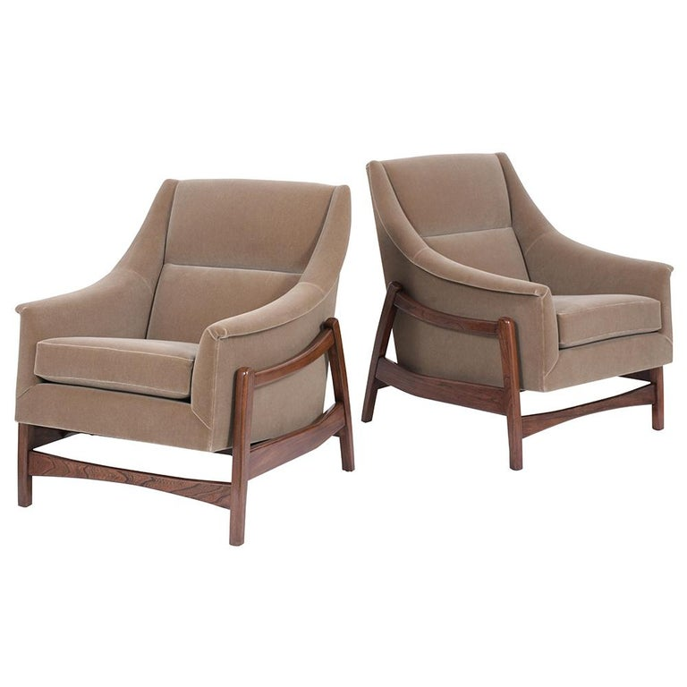 This remarkable 1960s pair of Mid-Century Modern Lounge Chairs are handcrafted out of teak wood, have a sleek design base, and the frame allows for the seat to rock with ease. These rocking chairs have been professionally reupholstered in beautiful