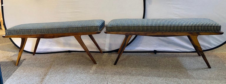 Pair of Mid-Century Modern rosewood benches refinished and reupholstered in a nice sleek fabric with blue and cream lines. These stylish and modern design window benches or footstools would make a Fine addition to any Mid-Century Modern setting.