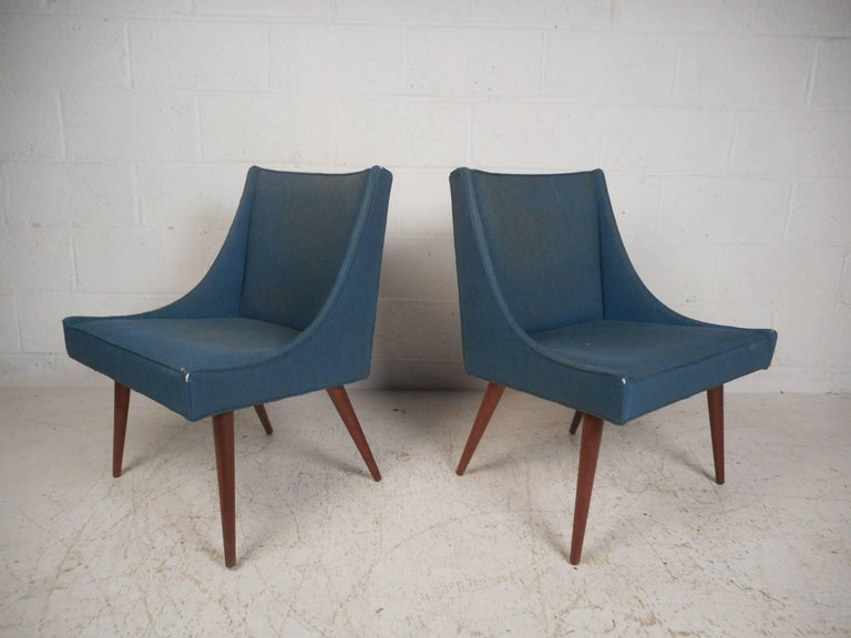 This gorgeous pair of vintage modern lounge chairs feature splayed walnut legs. A slipper style design covered in a vintage blue fabric ensures plenty of comfort without sacrificing style. This unique pair of chairs make the perfect addition to any