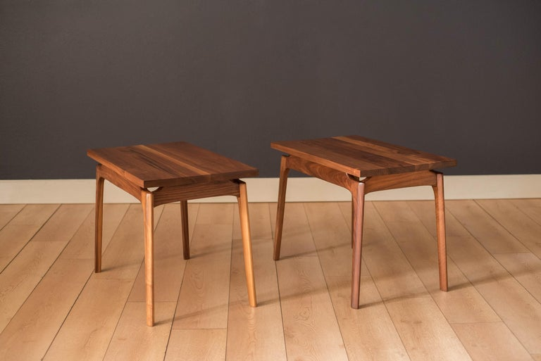 Vintage pair of side tables in solid planked walnut, circa 1960s. Features a floating tabletop design supported by contoured sculpted legs. Price is for the pair.