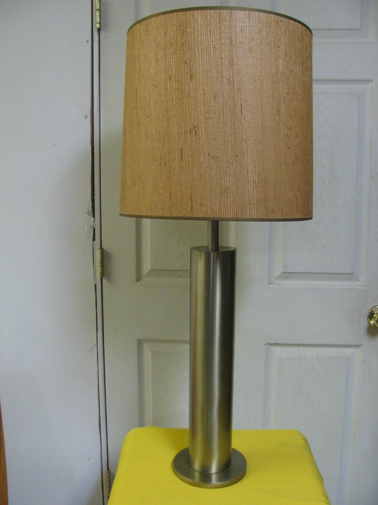 Pair of tall (28.5 inches to the top of the socket) elegant polished stainless steel lamps. Cylindrical form with no seams in the steel. These lamps would look great with black shades, which we do not have at this time. Shades not included.