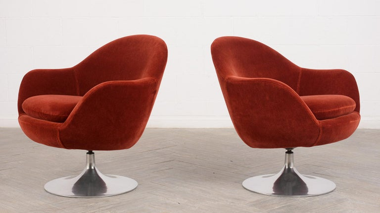 This pair of 1960s Mid-Century Modern style swivel lounge chairs are upholstered in a Red mohair velvet fabric with an aluminum base. The mohair covers all sides of the chairs and is in great condition. The comfortable seat has a single cushion and