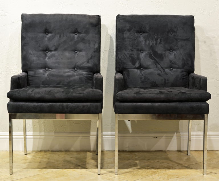 These armchairs or lounge chairs feature charcoal (with a slight bluish tint) tufted covered upholstery and elegant chrome frames and legs. A modern Classic.