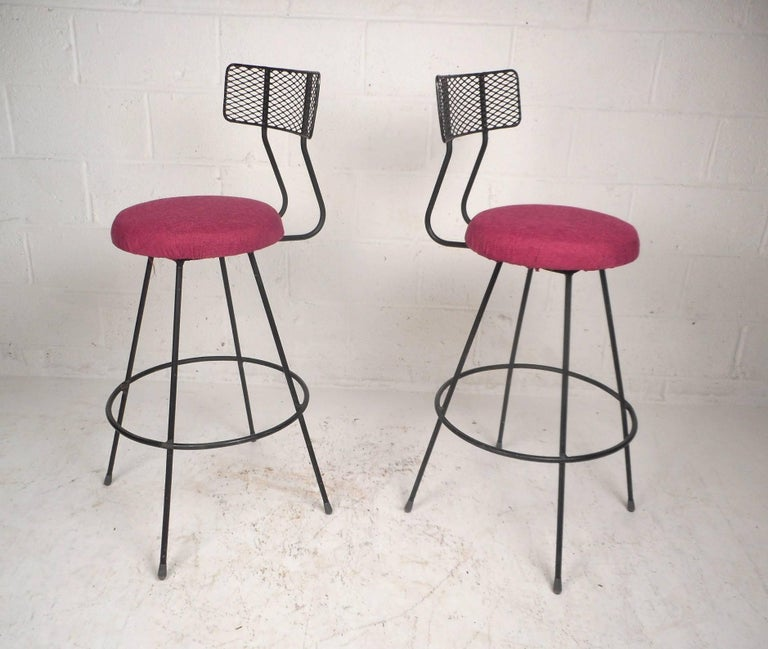 Stunning pair of vintage modern bar stools with grated metal back rests and iron rod bases. Wonderful design with a conveniently placed circular kick rest and long splayed legs. Sturdy construction and elaborate colorful upholstery make this