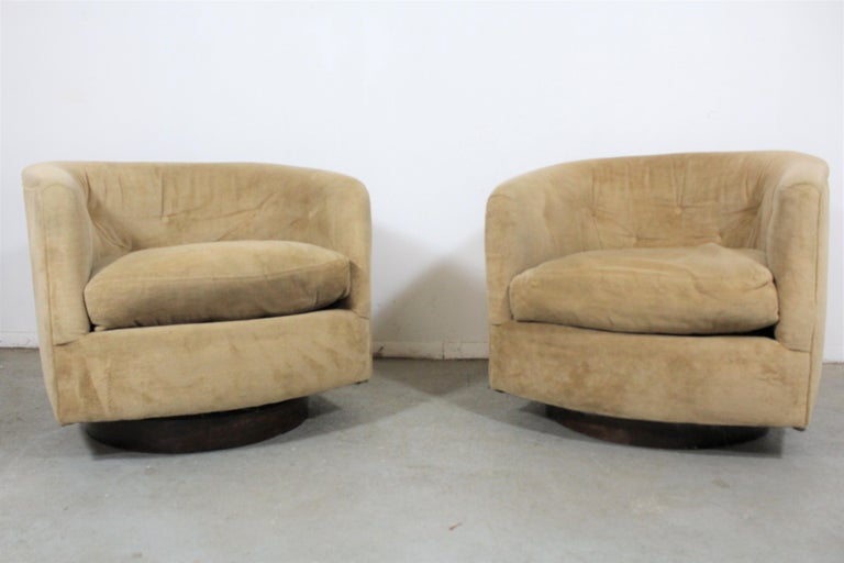 Pair of Mid-Century Modern swivel club chairs   What a find. Offered is a pair of swivel chairs on walnut bases. The upholstery is in usable condition and it is structurally sound. The walnut base has some surface scratches and age wear. They are