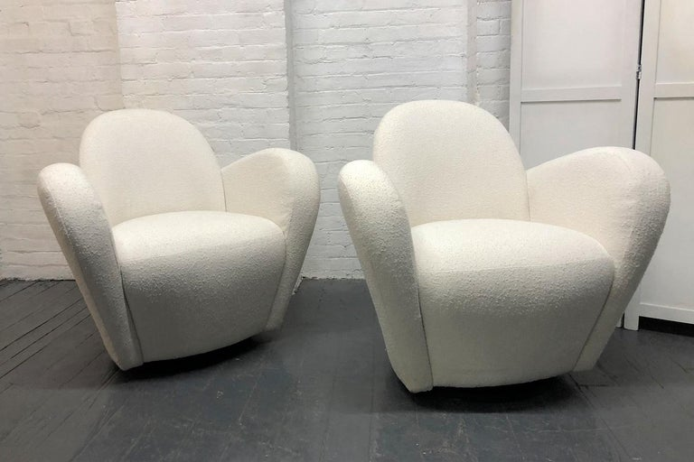 Pair of Vladimir Kagan for Directional swivel lounge chairs. The chairs are upholstered in an off-white bouclé fabric with black wooden swivel bases.
