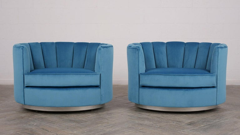 This pair of 1960s Mid-Century Modern style swivel chairs are upholstered on all sides in a beautiful peaceful sky blue velvet color fabric. The curved backs and arms feature a channel design that accents the profile of the chair. The seat is made