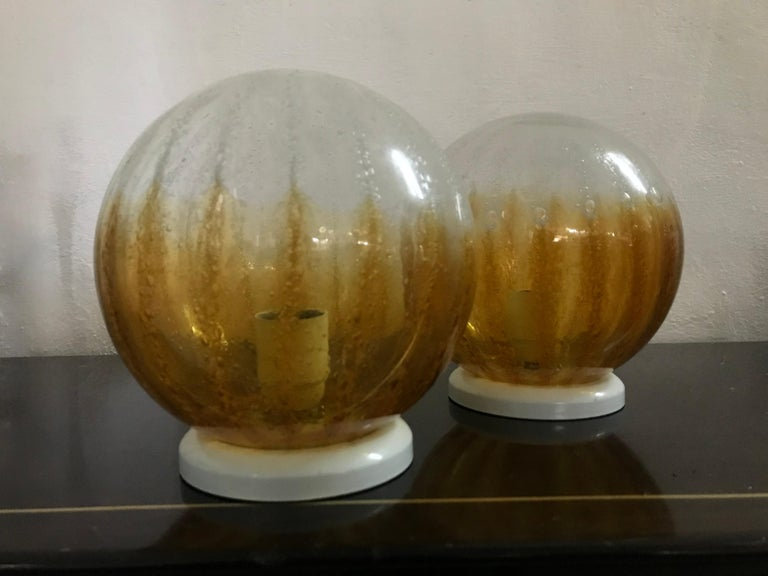 Pair of Space age one-light table lamps by Mazzega, circa 1960. Manufactured in clear, amber and bubble Murano glass.