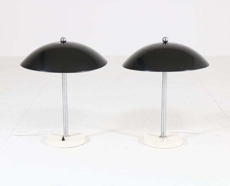 Wonderful pair of Mid-Century Modern model 5015 table lamps. Design by Wim Rietveld for Gispen. Striking Dutch design from the 1950s. Original black lacquered metal shades, one has a minor indentation on the top of the shade. In good original