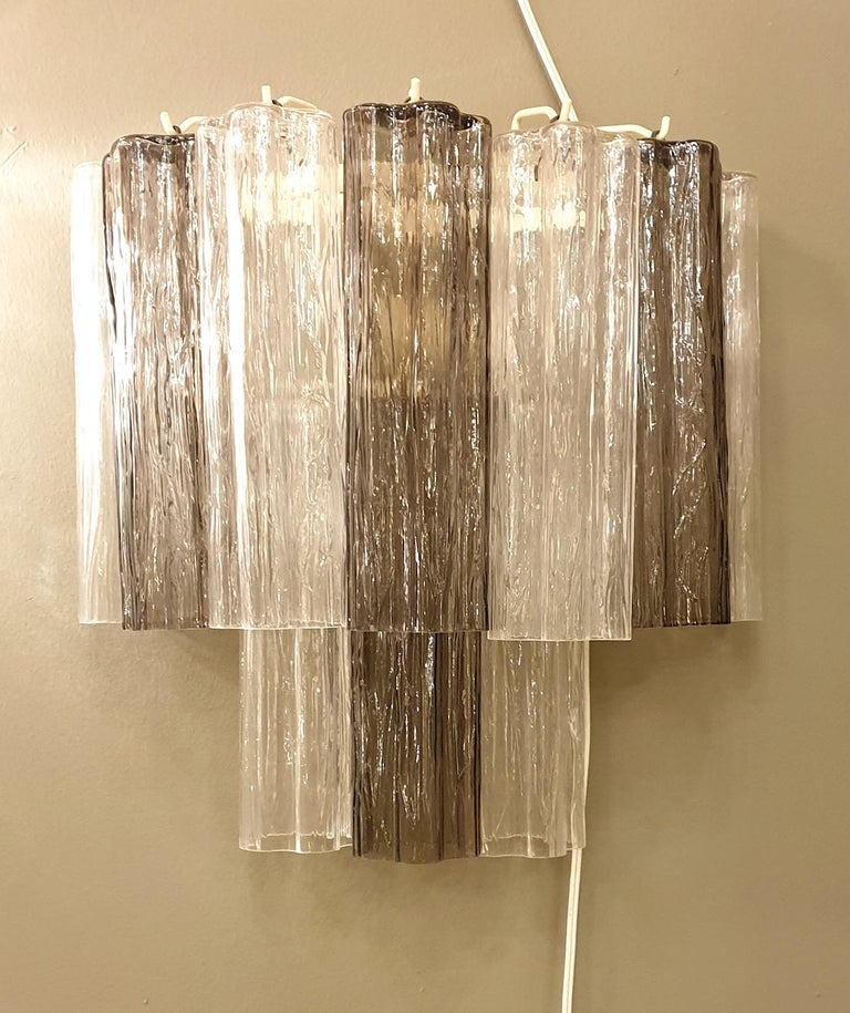 Pair of Mid-Century Modern two colors Venini Tronchi Murano glass sconces, Italy, 1970s. The pairs of sconces alternates transparent and beige colors of glass. The frame is painted in ivory The sconces have 2 lights each: rewired with candelabra