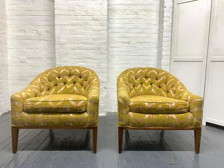 Pair of Mid-Century Modern tufted lounge chairs in the style of Dunbar. Original upholstery and wooden legs.