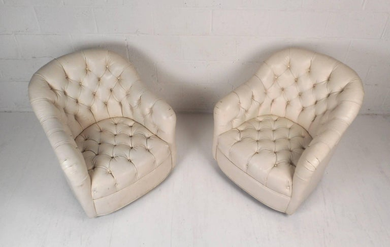 Stunning pair of vintage modern lounge chairs covered in white tufted vinyl. This wonderful pair has a comfortable barrel backrest with sloping arm rests. These stylish chairs have thick padded seating with deep tufts and wheels on the base ensuring
