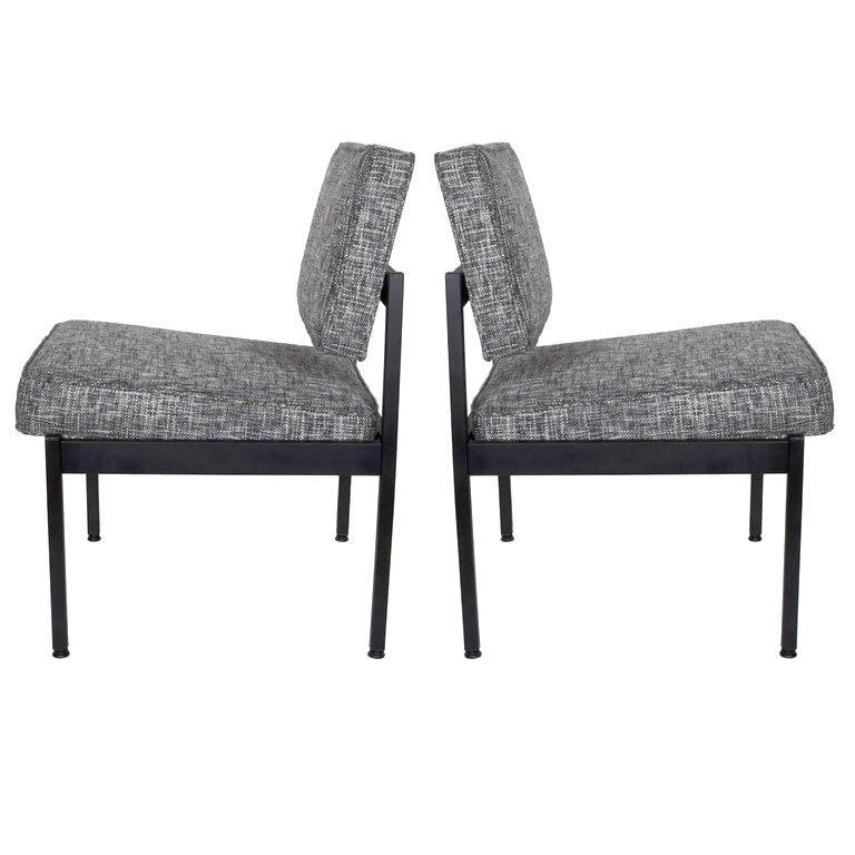 Pair of upholstered Mid-Century Modern industrial style chairs with floating seat and back cushions. Fine example of utilitarian furniture, great as office chairs or easy chairs. Satin black enameled metal frame is complimented by newly upholstered