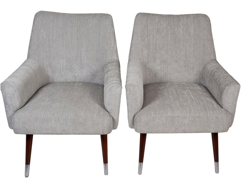 Pair of Mid-Century Modern armchairs with teak legs and chrome feet. European. Reupholstered in a soft gray silk linen. Refinished.