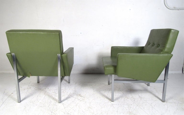 A beautiful pair of vintage modern armchairs with metal legs and tufted green vinyl upholstery. The wonderful design offers maximum comfort without sacrificing style. A perfect addition to any home, business, or office. Please confirm the item