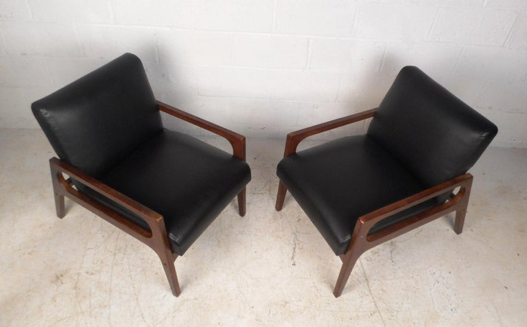 This stunning pair of vintage modern lounge chairs feature a sculpted walnut frame with low armrests and angled back legs. An extremely comfortable design with thick padded seating covered in black vinyl. This sleek and sturdy pair of midcentury