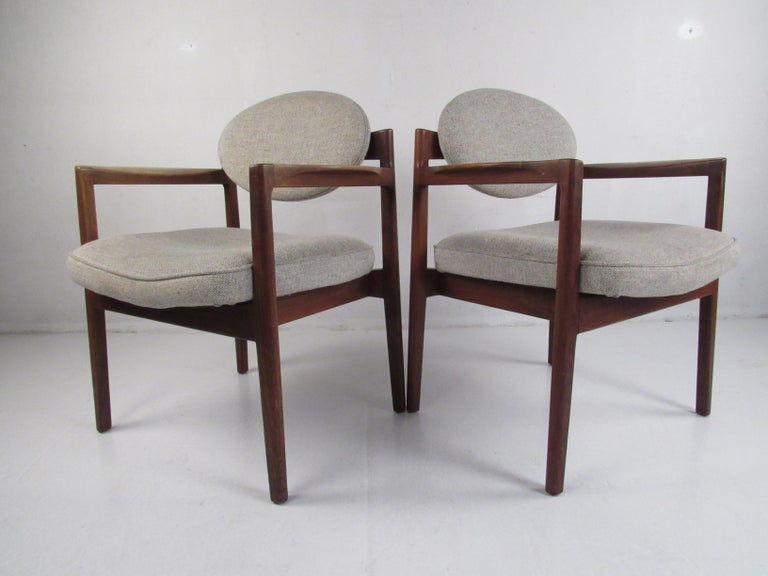 This beautiful pair of vintage modern arm chairs boast sculpted arm rests, tapered legs, and soft light gray upholstery. An extremely unique design with floating circular back rests and thick padded seating. Quality craftsmanship with straight lines