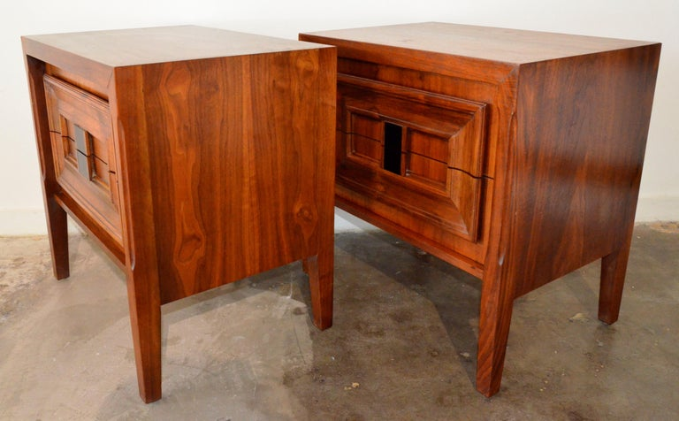 Offered are a pair of Mid-Century Modern Brutalist walnut veneer and burl wood bedside night stands / side or end tables. The bedside tables are box two-drawer cabinets on raised legs. The burl wood on these bedside stands / tables make for a