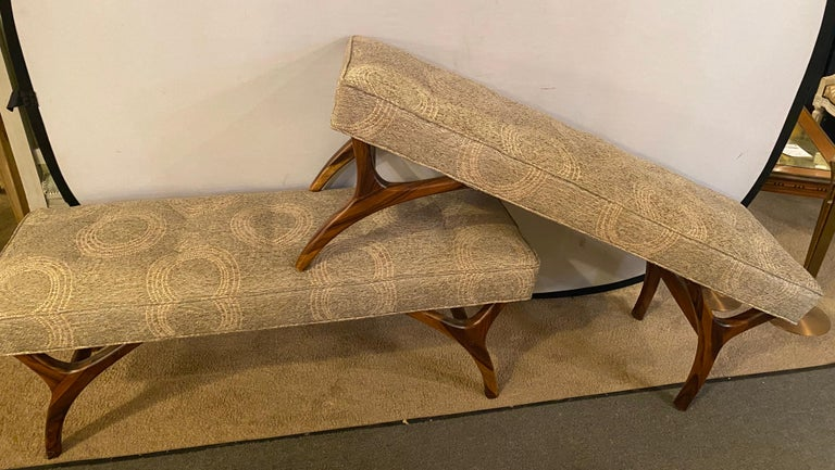 Pair of Mid-Century Modern window benches or stools in a new upholstery with new welts and springs. The fine rosewood like carved legs supporting a comfortable and recently upholstered seat.