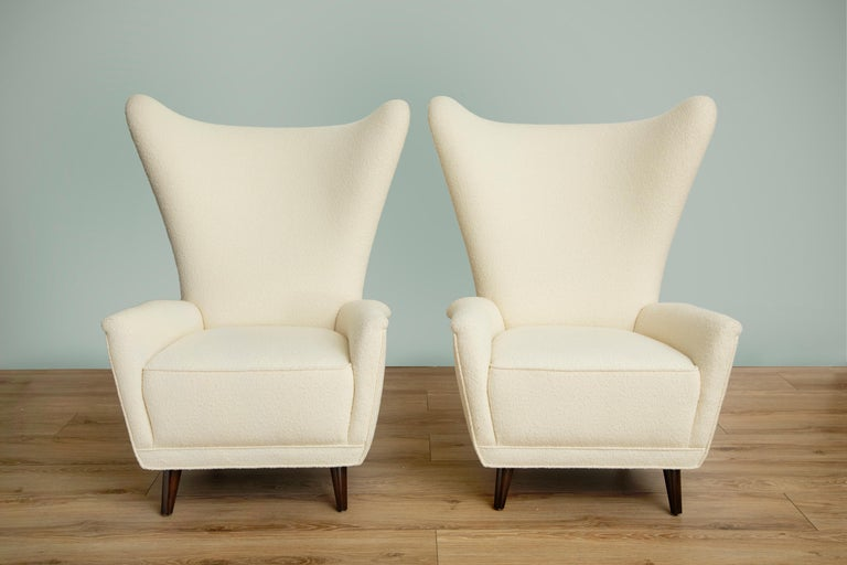 Pair of Mid-Century Modern wingback lounge chairs in the style of Gio Ponti, High backrest with curvaceous wings and gently curved armrests, Comfortable Classic lounge chair newly upholstered in pearl bouclé by Knoll, Ebonized conical wood