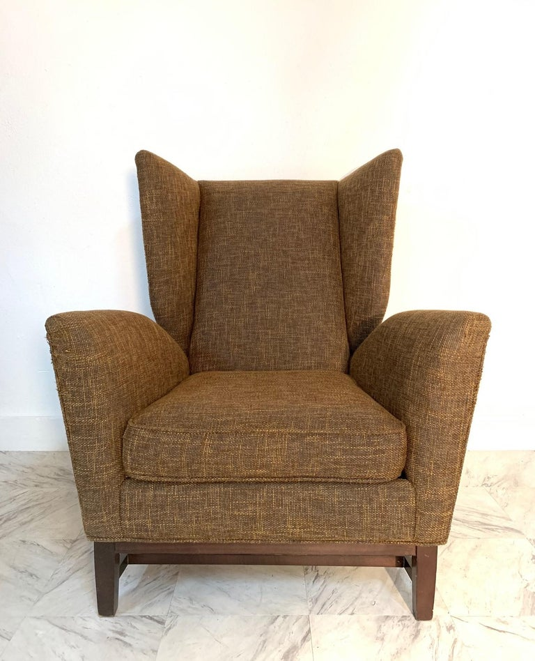 Pair of Italian Mid-Century Modern wingback lounge chairs. Has a solid walnut base.