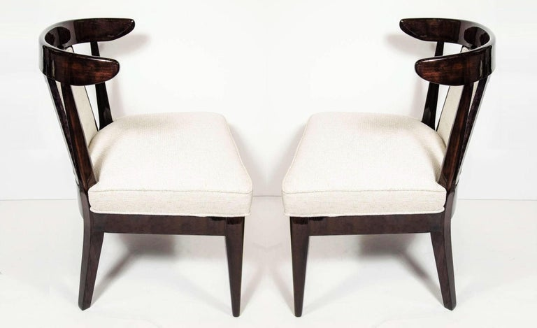 These very sophisticated pair of low profile chairs are a perfect blend of Hollywood Glam and Mid-Century Modern design. Featuring ebonized walnut klismos form frames with upholstered splat backs and seats that rise above tapered legs. Beautifully