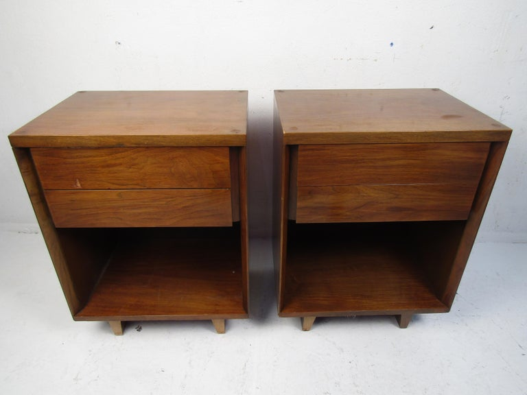Stylish midcentury nightstands sold by John Stuart. Two dovetail jointed drawers on each, with open storage space beneath. Please confirm item location with dealer (NJ or NY).