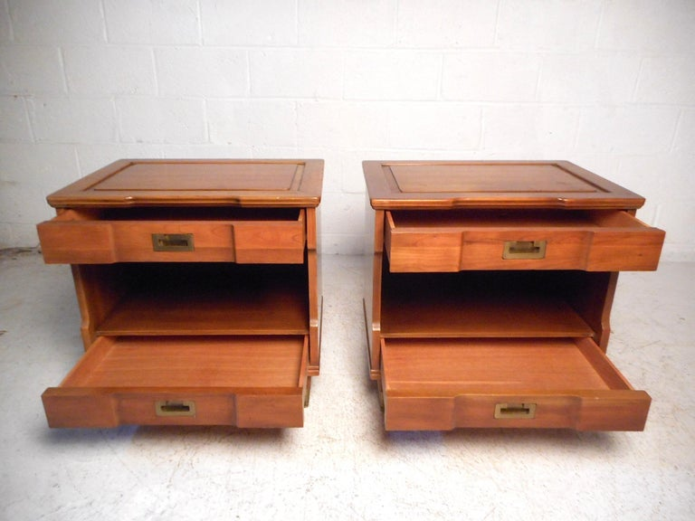 This stylish pair of vintage modern nightstands feature a sturdy walnut construction with a lightly colored finish, two drawers with dovetail wood-joints signifying quality craftsmanship while offering ample storage space, brass Campaign style