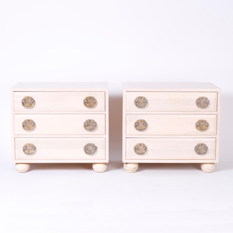 Vogue pair of midcentury three-drawer night stands or chests with an unusual pickled pine finish, sleek Asian Modern form, speckled brass Ming style hardware, and proper bun feet.