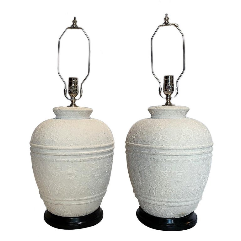 A pair of 1950s plaster table lamps with ebonized bases.  Measurements: Height of body 15