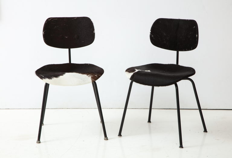 A pair of midcentury four legged SE - 68 chairs in original cowhide by German architect and designer Egon Eiermann.