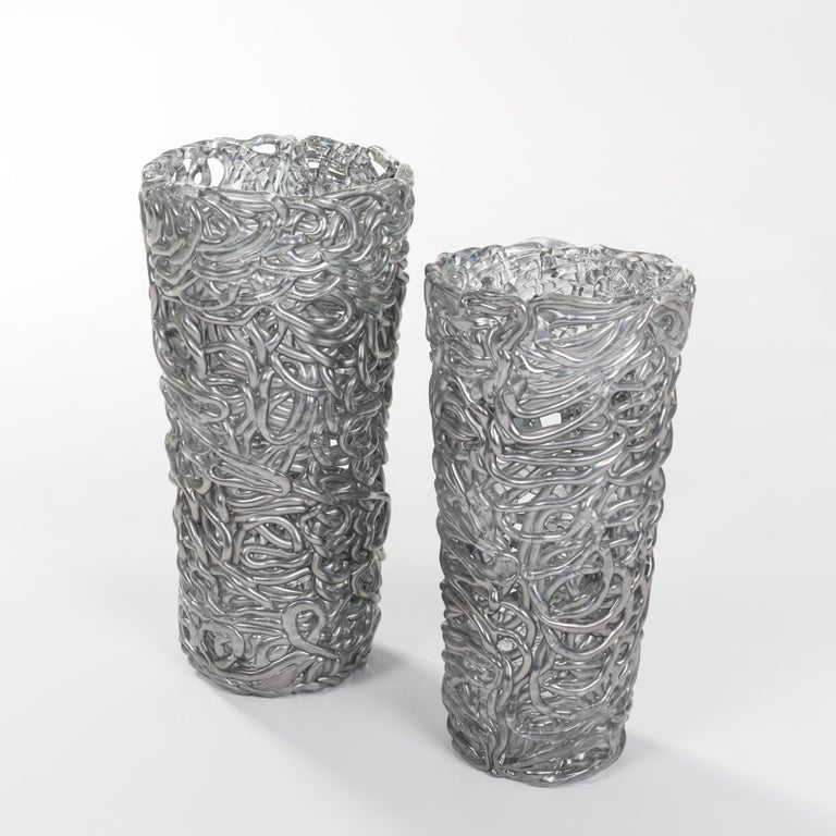 Exceptional pair of silver-colored Murano glass vases. Intertwined glass veins shape the outer wall. There is little space between the glass veins Undamaged original condition. Size 1: height 44cm x diameter above 22cm x diameter below 16cm Size 2: